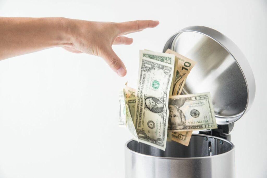 Hand throwing money away